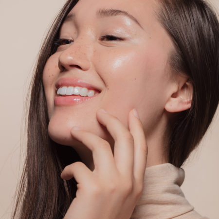 Close up of beautiful woman touching her face. Asian woman with perfect healthy skin.